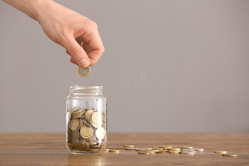 Man putting coins into glass jar on table. Savings concept royalty free stock images