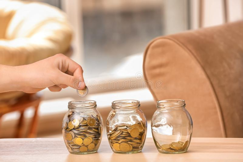 Man putting coins into glass jars on table. Savings concept stock images
