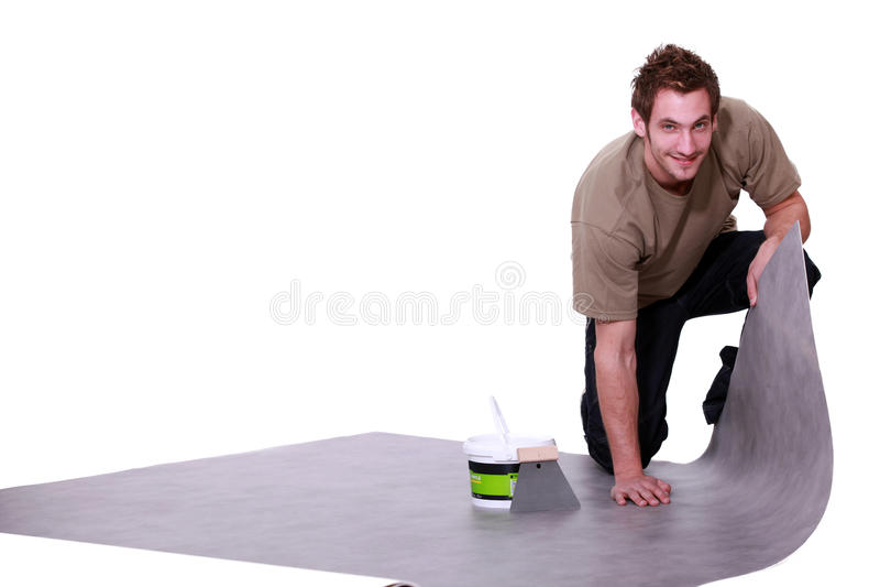 Man putting down flooring. Man putting down linoleum flooring stock image