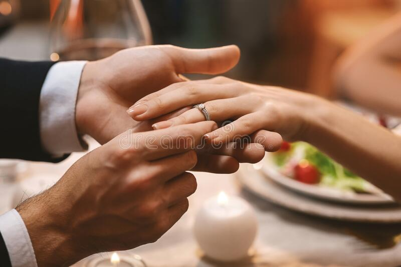 Man Putting Engagement Ring On Girfriend`s Finger After Proposal In Restaurant royalty free stock image