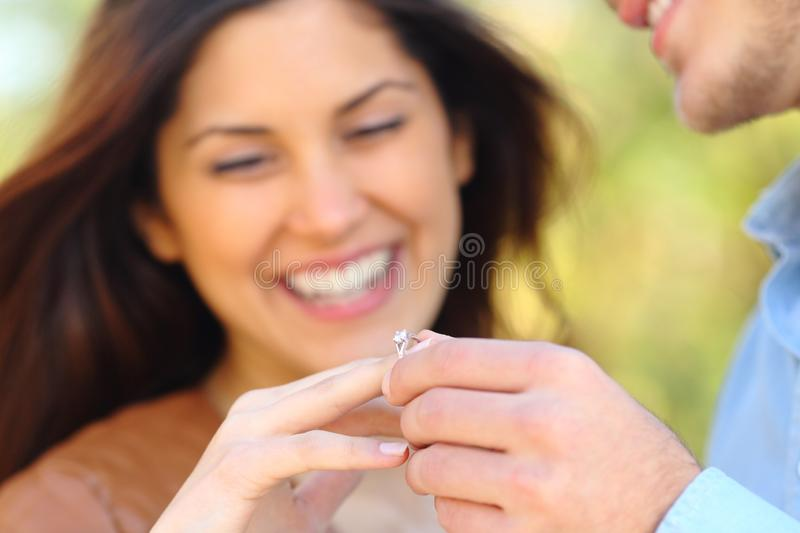 Man putting engagement ring to his glad girlfriend royalty free stock photos
