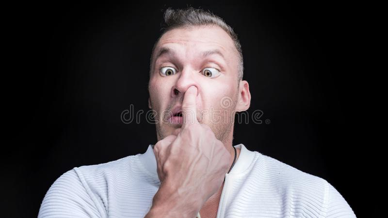 Man putting finger deep in his nose. Bad habit concept royalty free stock photography