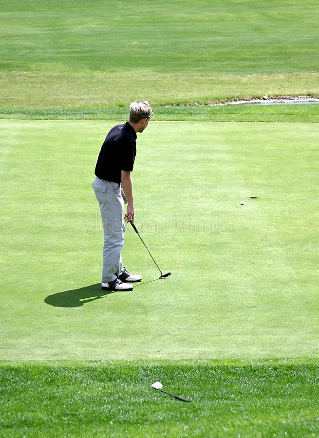 Man putting on green during game of golf royalty free stock photo