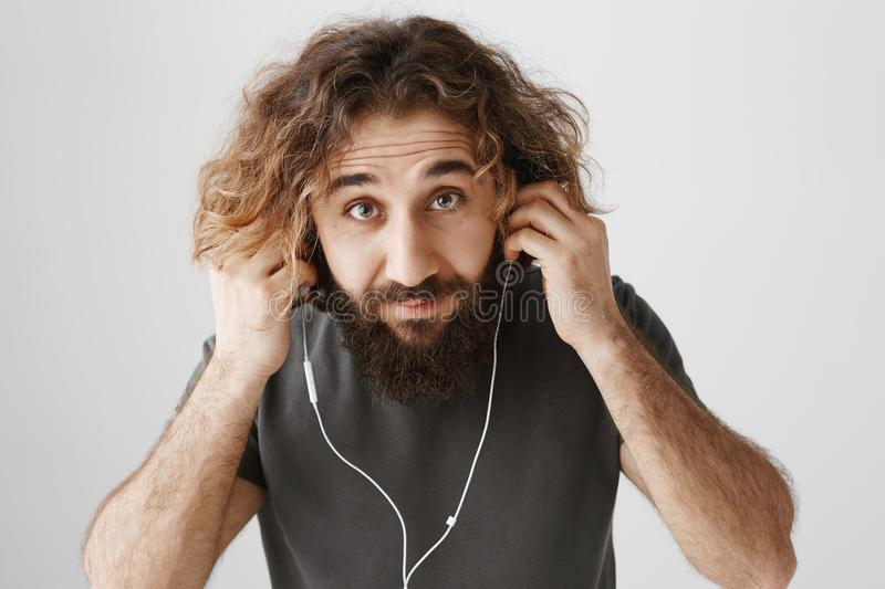 Man is putting on headphones to go jogging. Studio shot of handsome curly-haired eastern guy with beard listening music stock images