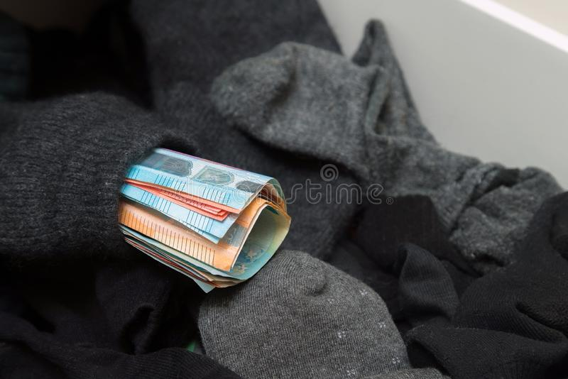 Man putting, hiding money in his socks to save it. Showing no tr. Ust in financial institutions and banks, black market royalty free stock photo