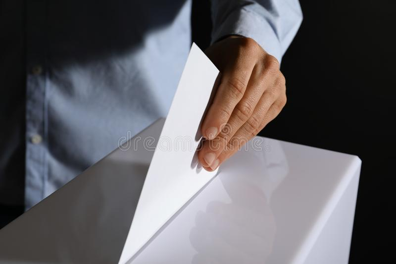 Man putting his vote into ballot box on black background royalty free stock photography