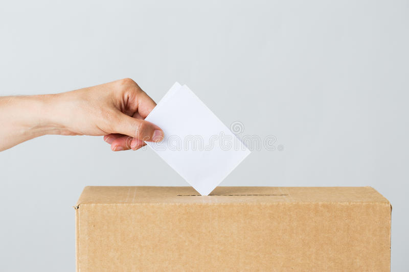 Man putting his vote into ballot box on election. Voting, civil rights and people concept - male hand putting his vote into ballot box on election royalty free stock photo