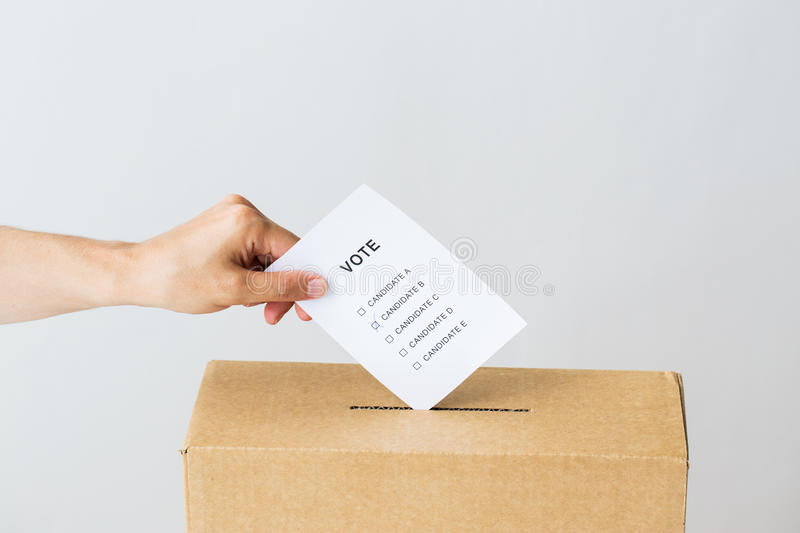 Man putting his vote into ballot box on election. Voting, civil rights and people concept - male hand putting vote into ballot box on election stock photos