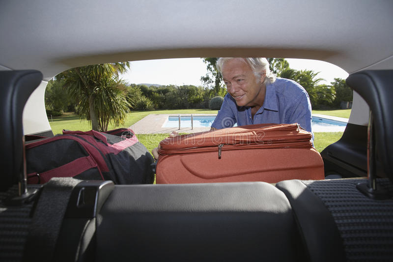 Download Man Putting Luggage Into Car Boot Stock Image - Image: 33892531