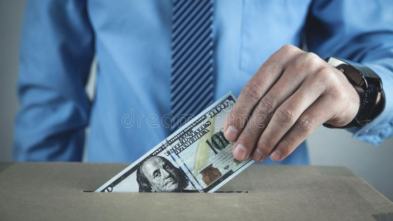 Man putting money on cardboard box. Save money royalty free stock photo
