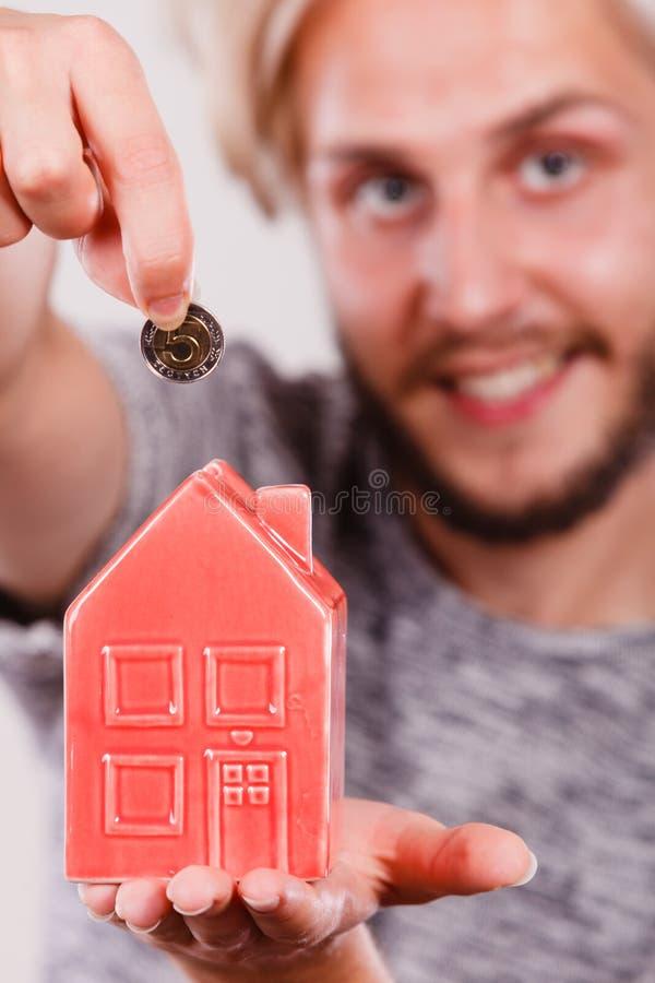 Man putting money into house piggybank stock photo