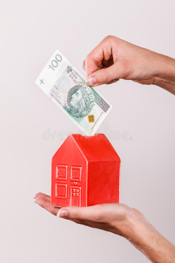 Download Man Putting Money Into House Piggybank Stock Image - Image: 83714359