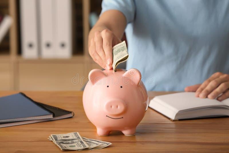 Man putting money into piggy bank. Savings concept royalty free stock photography