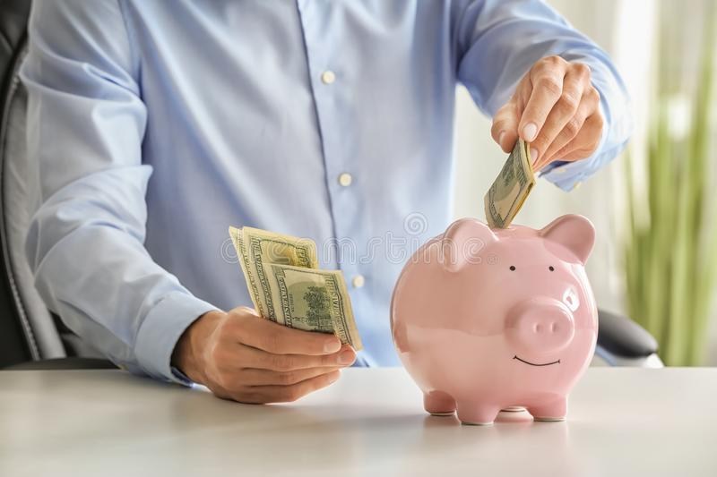 Man putting money into piggy bank. Savings concept royalty free stock images