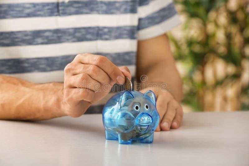 Man putting money into piggy bank. Savings concept stock images