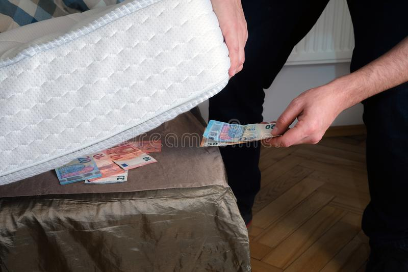 Man putting money under his mattress to save it. Showing no trust in financial institutions and banks, black market.  royalty free stock photography