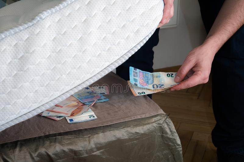 Man putting money under his mattress to save it. Showing no trust in financial institutions and banks, black market.  royalty free stock images