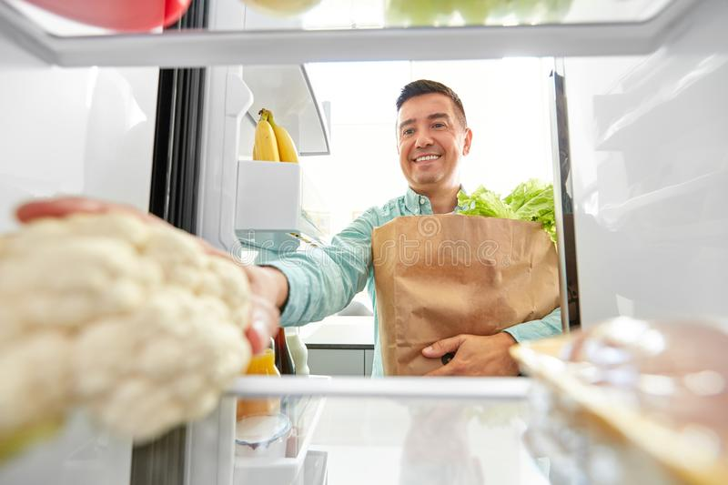 Man putting new purchased food to home fridge stock photo