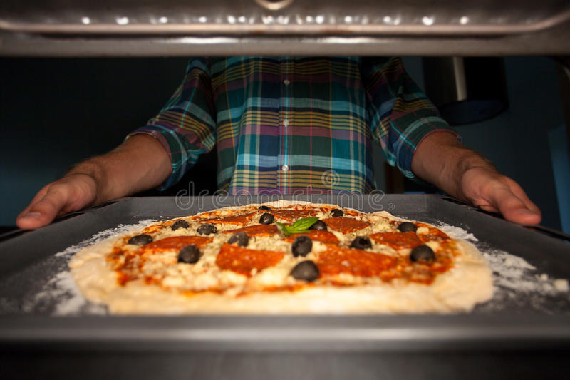 Man putting pizza into oven royalty free stock photography
