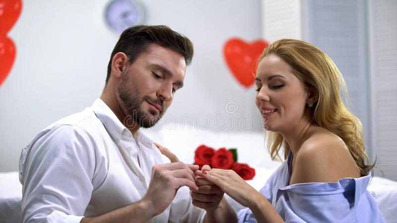 Man putting precious engagement ring on happy female finger, making proposal stock photography