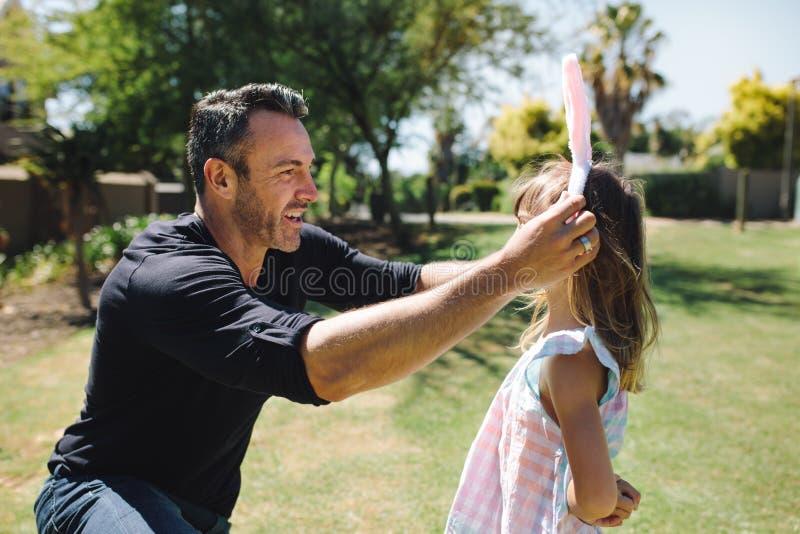 Man putting a rabbit ear headband on her daughter stock photos