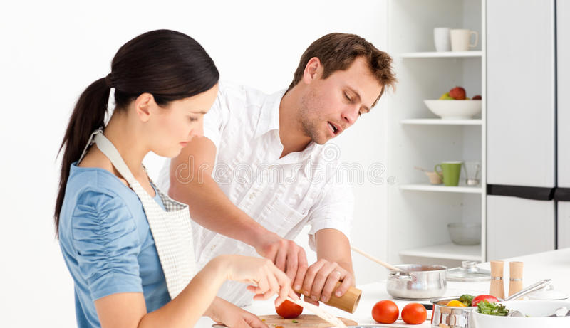 Man putting salt and pepper with his wife royalty free stock photos