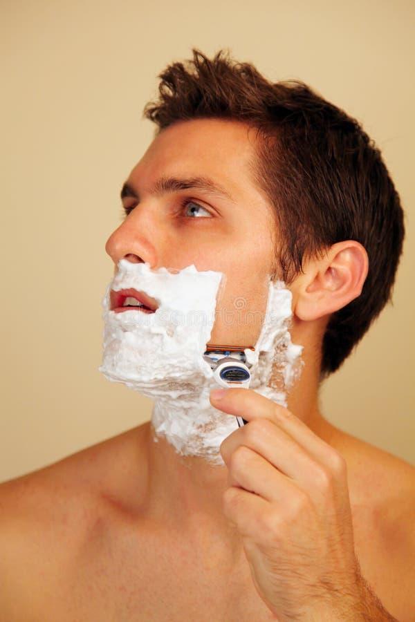 Man putting on shaving cream. Man putting shaving cream on his face stock images