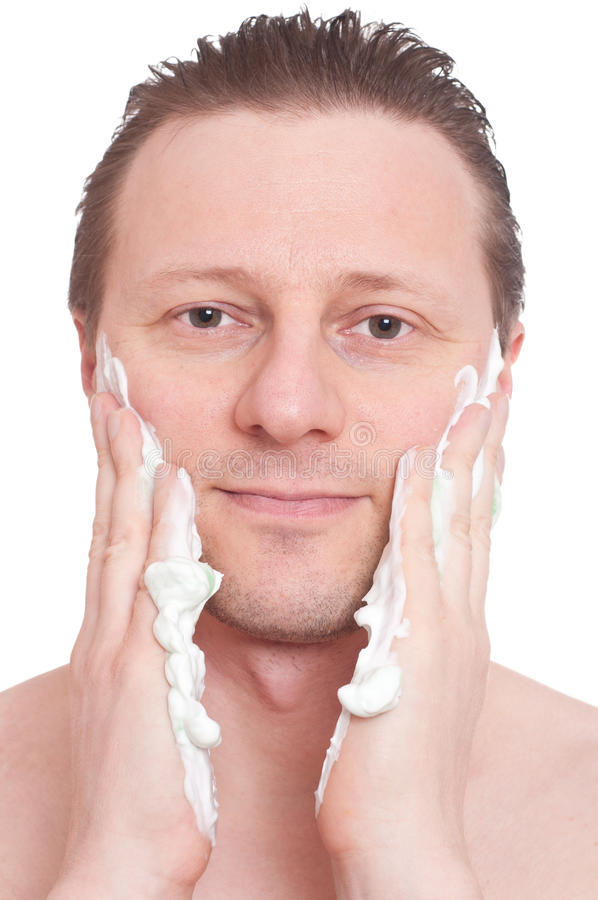 Man is putting shaving foam on his cheeks stock photo
