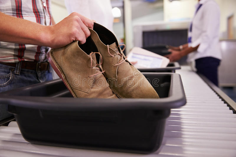 Man Putting Shoes Into Tray For Airport Security Check royalty free stock photo