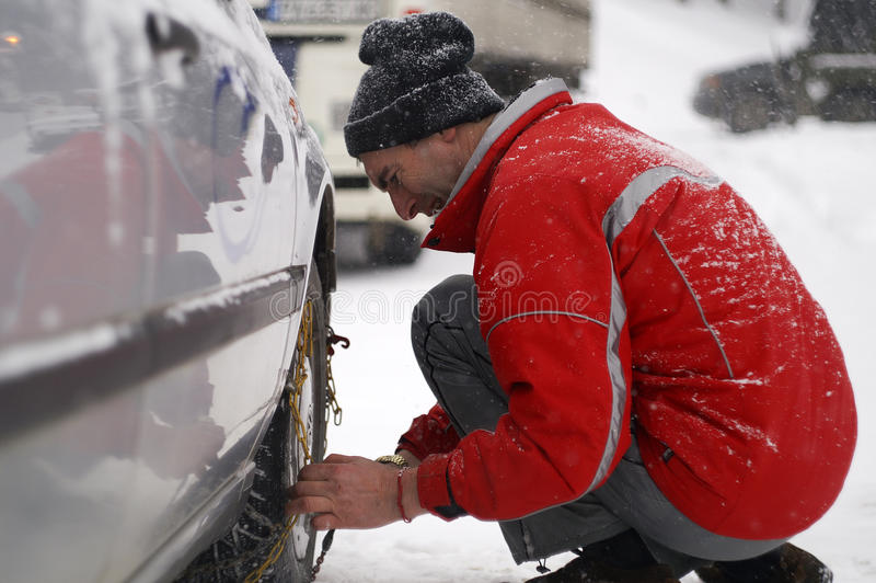 Man Putting Snow Chains On Car Tire Royalty Free Stock Images
