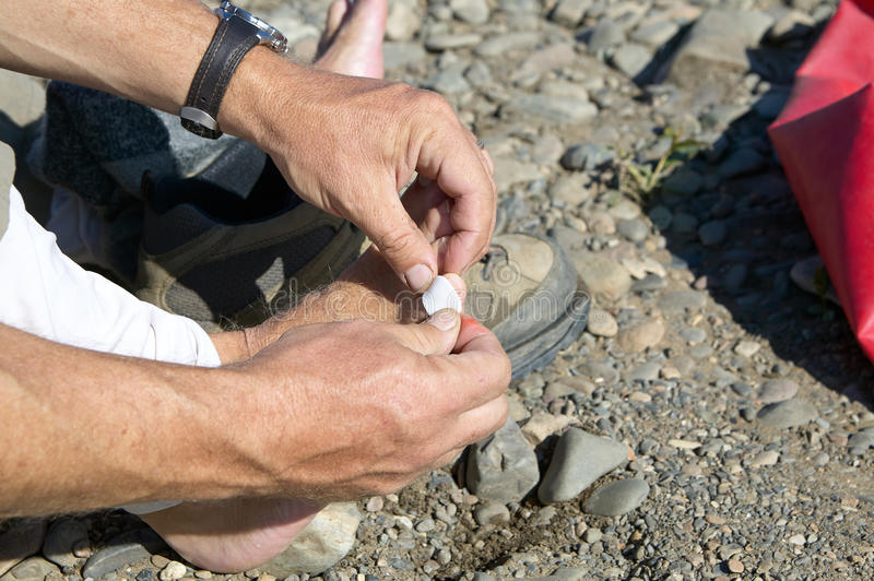 Man putting a sticking plaster on his toe. To treat a blister caused by his hiking boots or other small injury in a close up view of his hands stock image