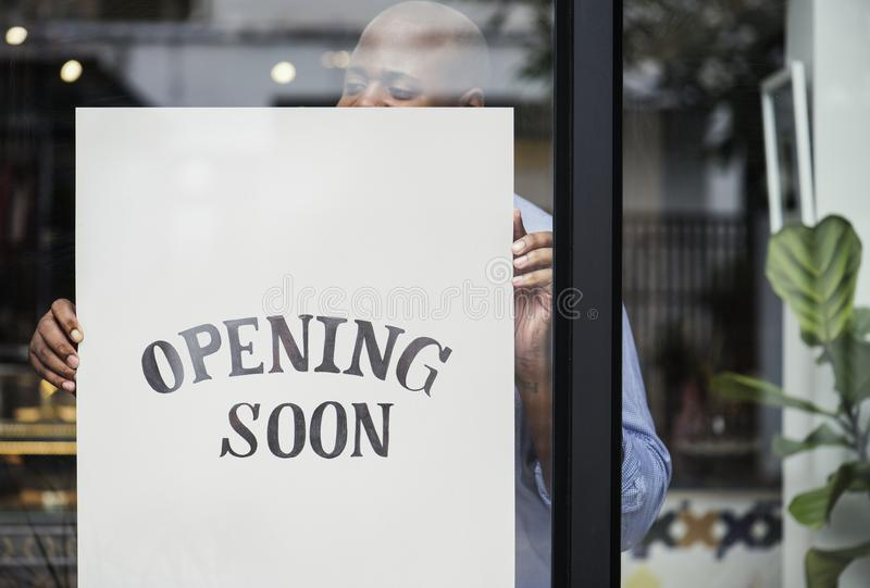 Man putting on store opening soon sign royalty free stock photo
