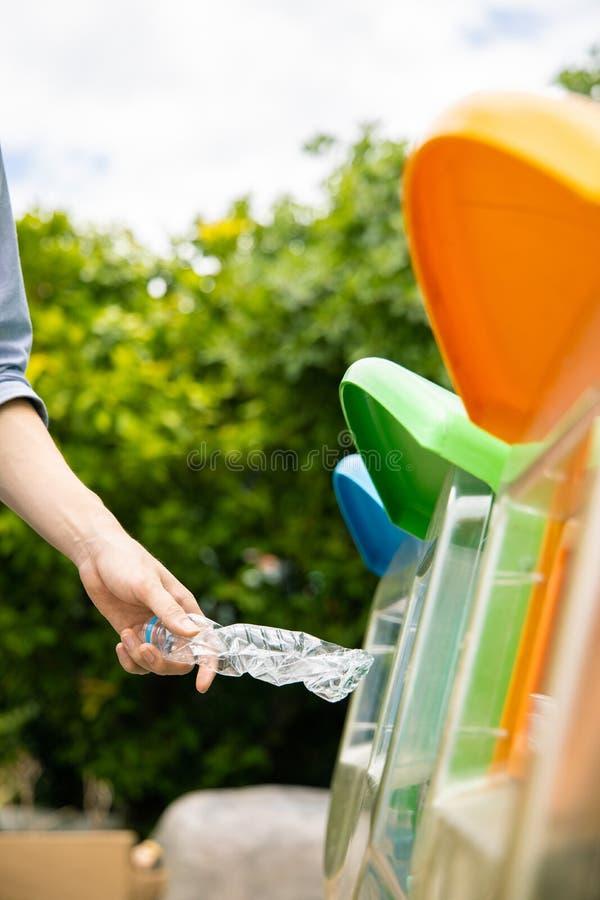 Man putting twisted bottle into bin. Man putting twisted plastic drinking water bottle into recycle bin in park, close up shot royalty free stock photo