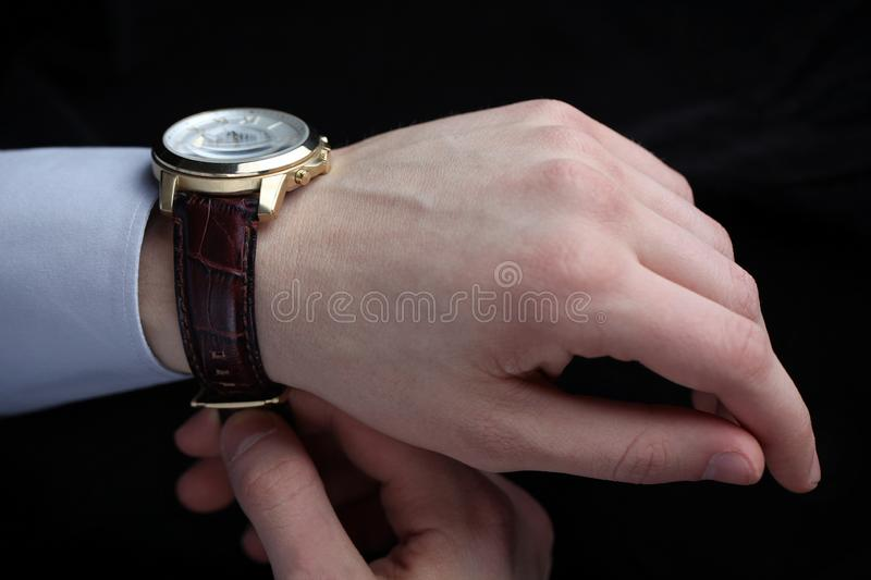 Man putting on wrist watch. Isoalted on black background. Shallow focus royalty free stock photography