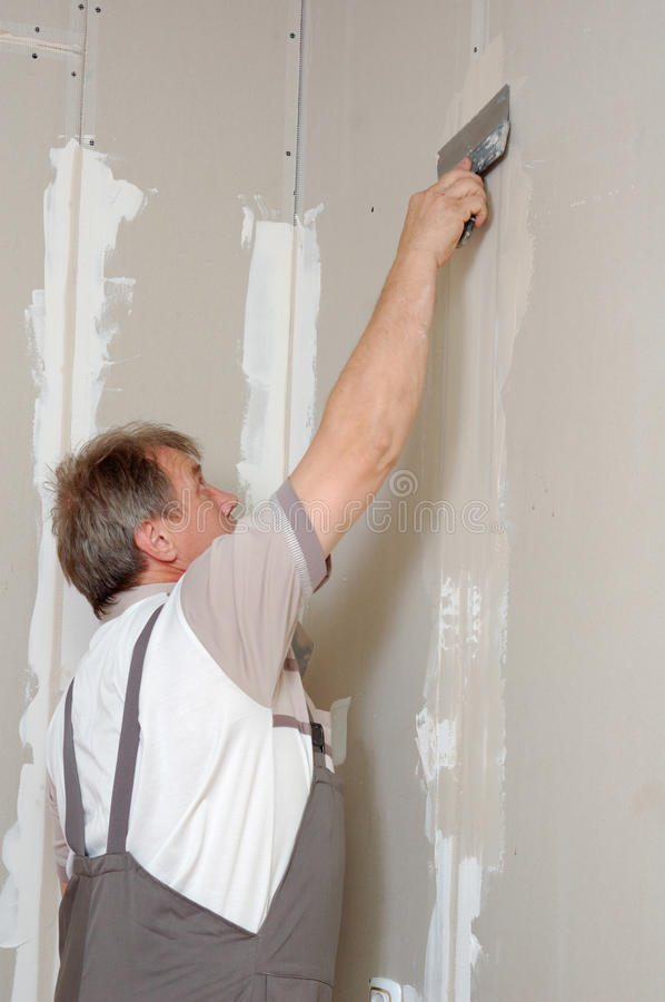 Man putty plasterboard royalty free stock photos