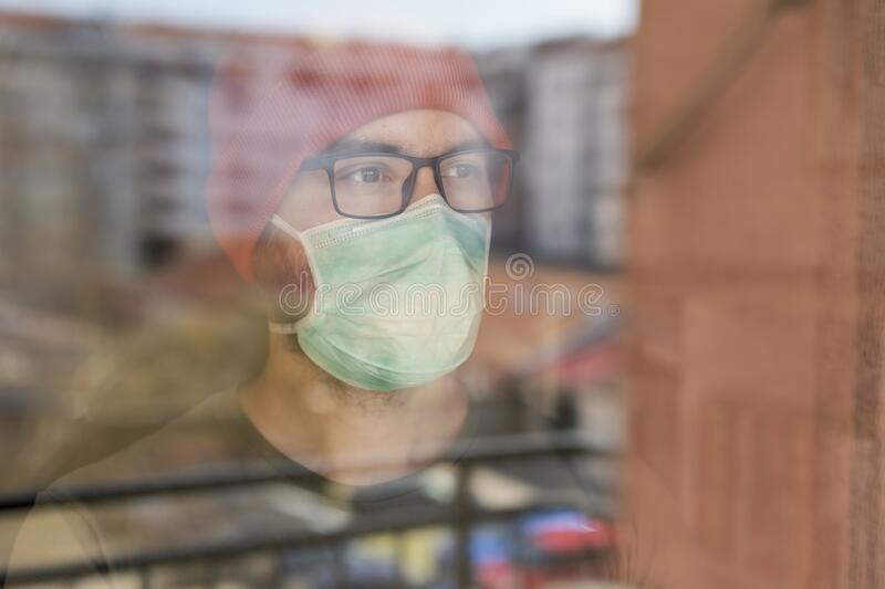 Man in quarantine during coronavirus outbreak. Portrait of a man standing inside his apartment, looking out of the window, wearing medical face protection mask royalty free stock photos
