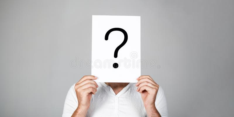 Man a question. Doubtful man holding Question Mark. Problems and solutions. Question mark, symbol. Pensive male. Getting. Answers. Portrait of man, peeking royalty free stock photo