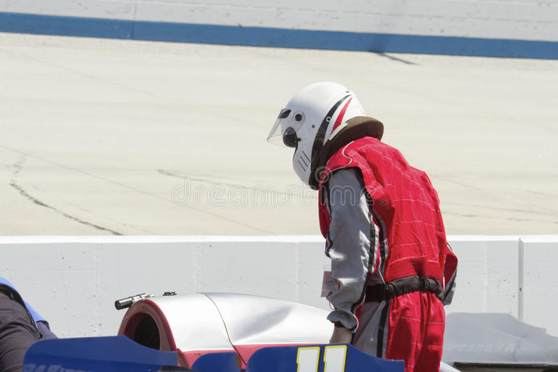 Man in race suit on pit row with IRL car. Man in race suit and helmet next to IRL race car on pit row at Motor Speedway stock photos