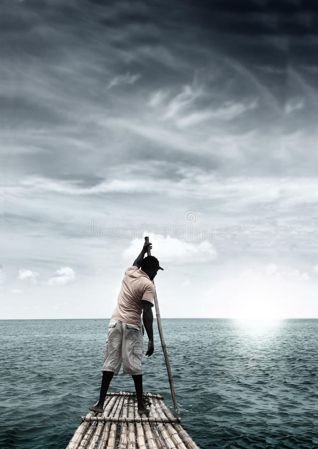 Man on raft. In the middle of a tropical ocean paradise with dramatic sky royalty free stock image