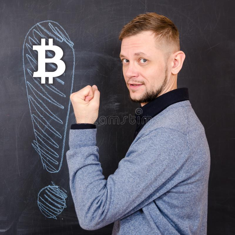Man with a raised hand near the black school board on which is drawn an exclamation mark and a symbol of bitcoin royalty free stock image