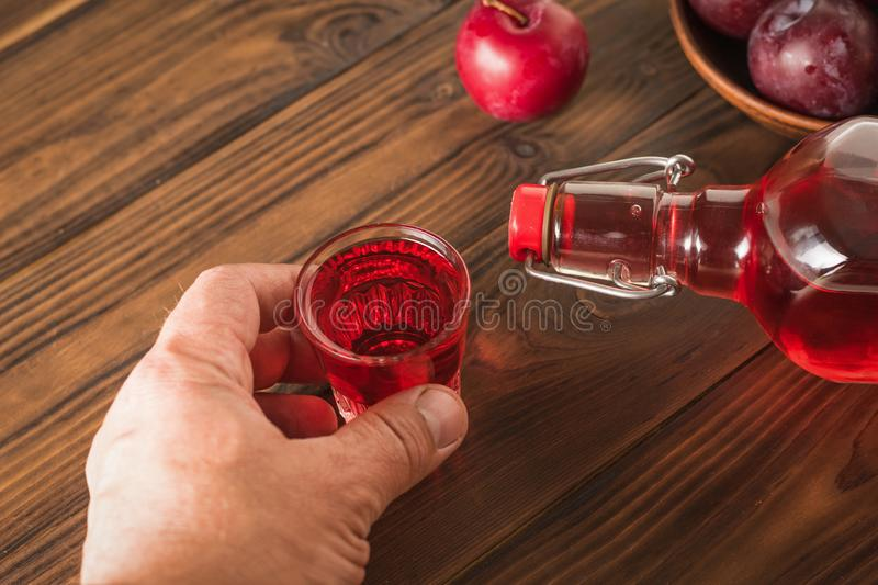 A man raises a glass of plum liqueur over a wooden table. Homemade alcoholic drink made from berries plum stock photography