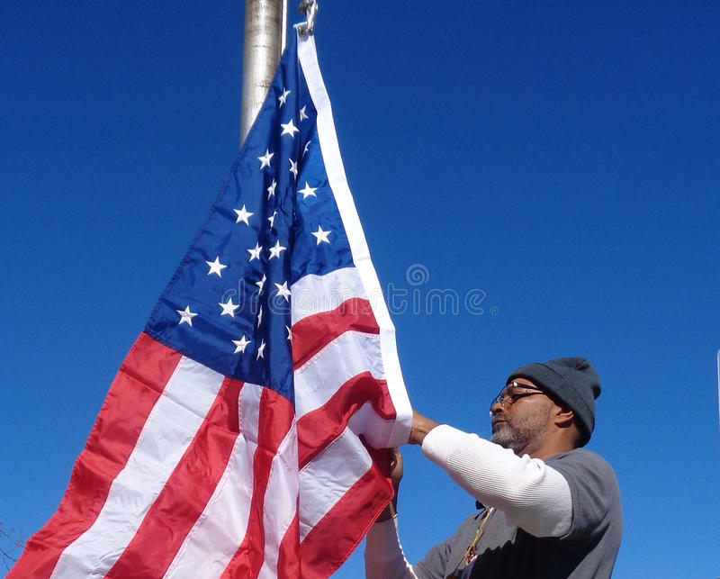 Man Raising the American Flag. This is an image of an African American man raising a United States Flag in the bright morning sun. A brilliant blue sky in the stock image