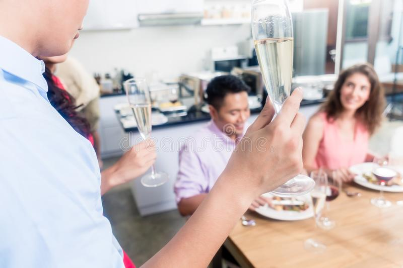 Man raising champagne flute toast with friends. Close-up of a men raising champagne flute toast with friends at home stock photo