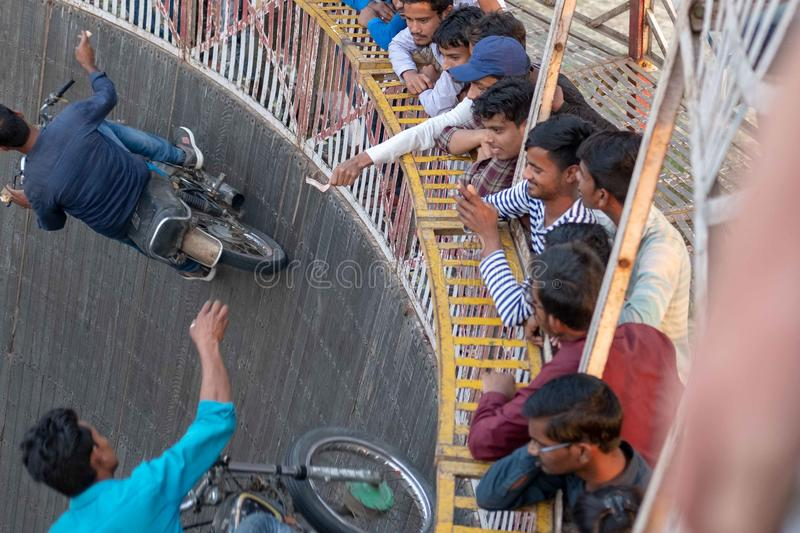 A man reaches for tips dangled by spectators while riding the wall of death at a f. Bhadarsa, Uttar Pradesh / India - April 5, 2019:A man reaches for tips royalty free stock photography