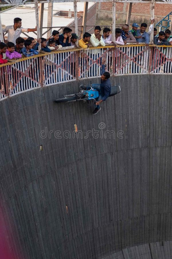 A man reaches for tips dangled by spectators while riding the wall of death at a f. Bhadarsa, Uttar Pradesh / India - April 5, 2019:A man reaches for tips royalty free stock photos