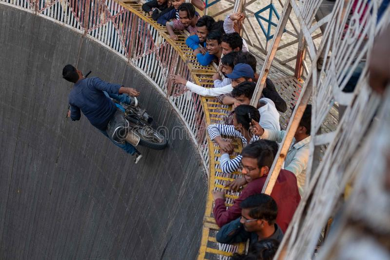 A man reaches for tips dangled by spectators while riding the wall of death at a f. Bhadarsa, Uttar Pradesh / India - April 5, 2019:A man reaches for tips stock images