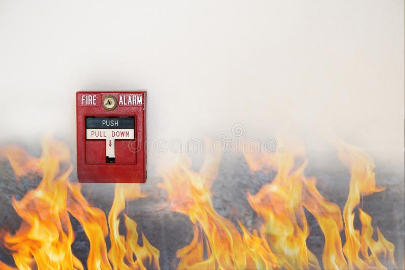Hand of man pulling fire alarm switch on the white wall as background for emergency case at the new factory building. Man is reaching his hand to push fire royalty free stock image