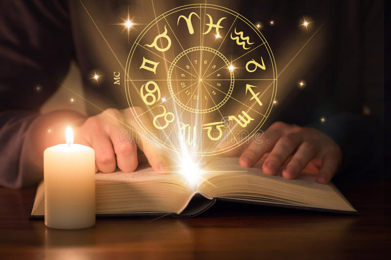 Man reading astrology book. With candle royalty free stock images