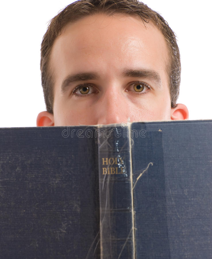 Man Reading Bible. A young man reading his bible with hald his head behind it, isolated against a white background royalty free stock photos