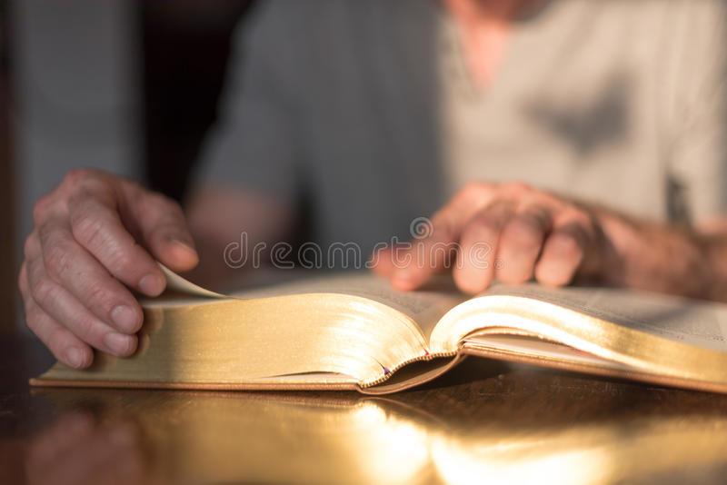 Man reading the Bible. In dim light royalty free stock photo